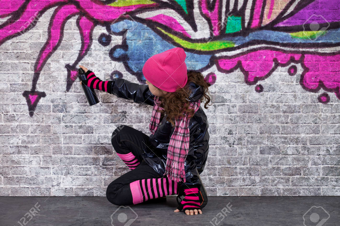 adolescente nia pintando un graffiti en una pared foto de archivo