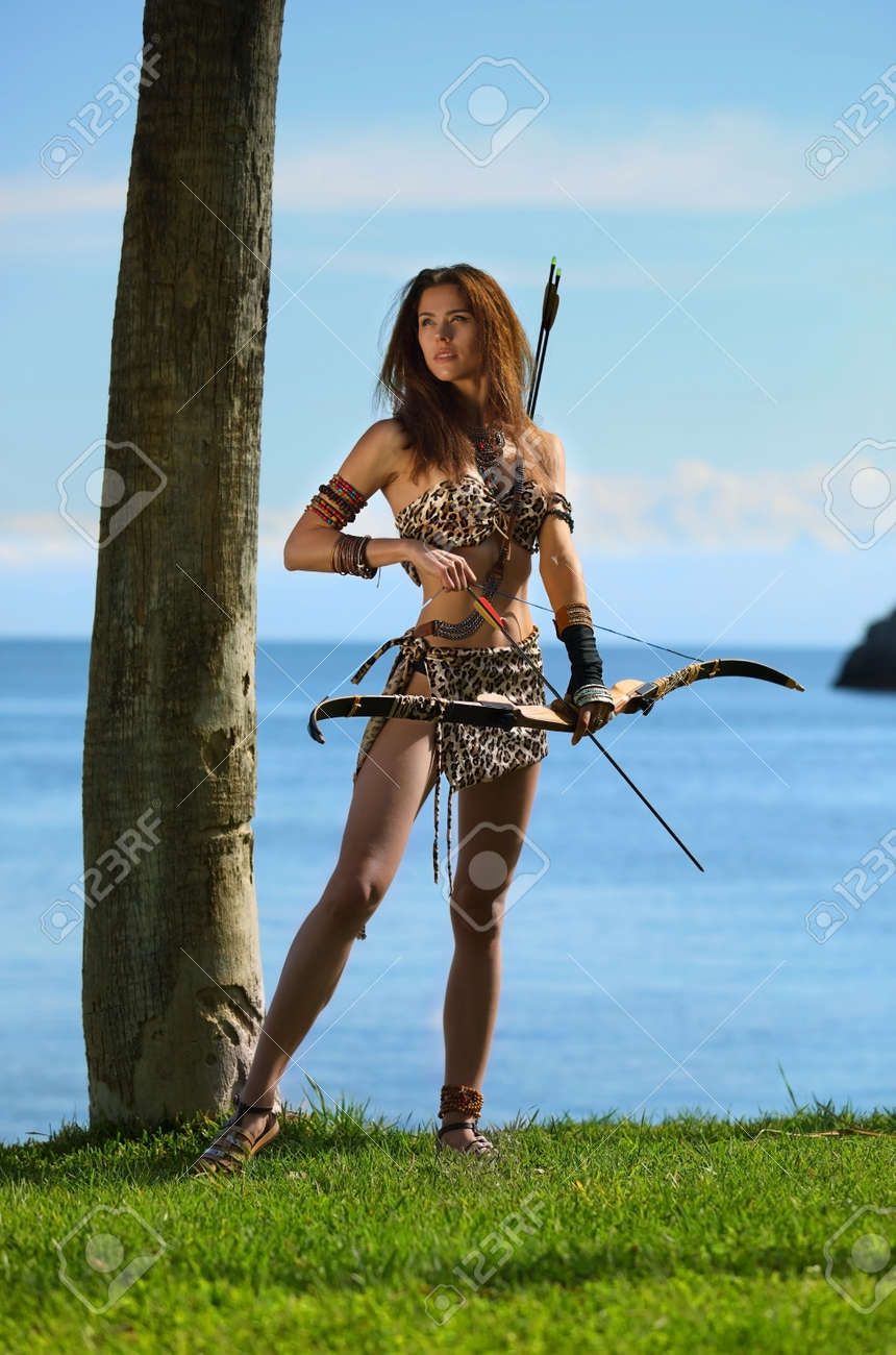 A young beautiful girl in an Amazon costume with a bow and arrows on a background of sea and blue sky - 122279673