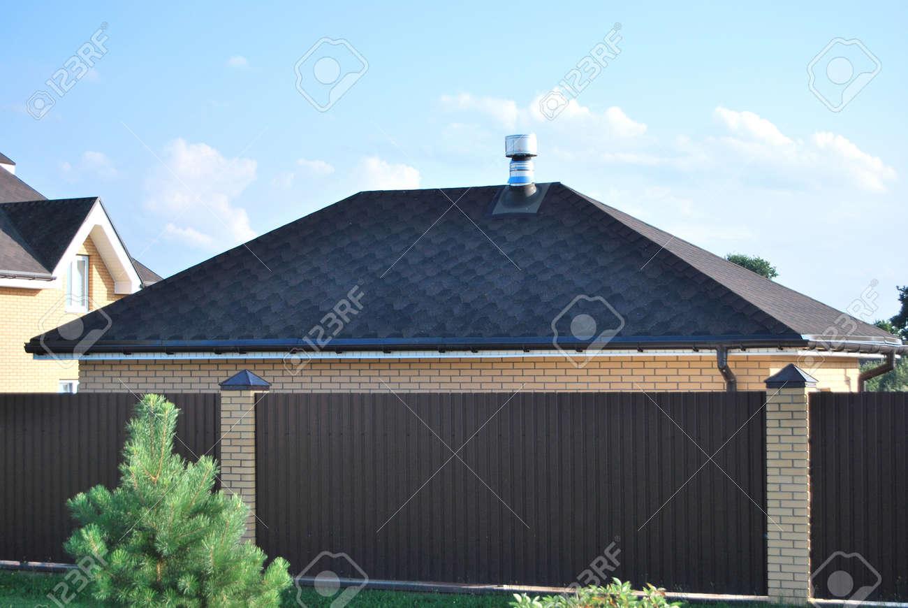 Il tetto del garage coperto di piastrelle scure morbide in primo
