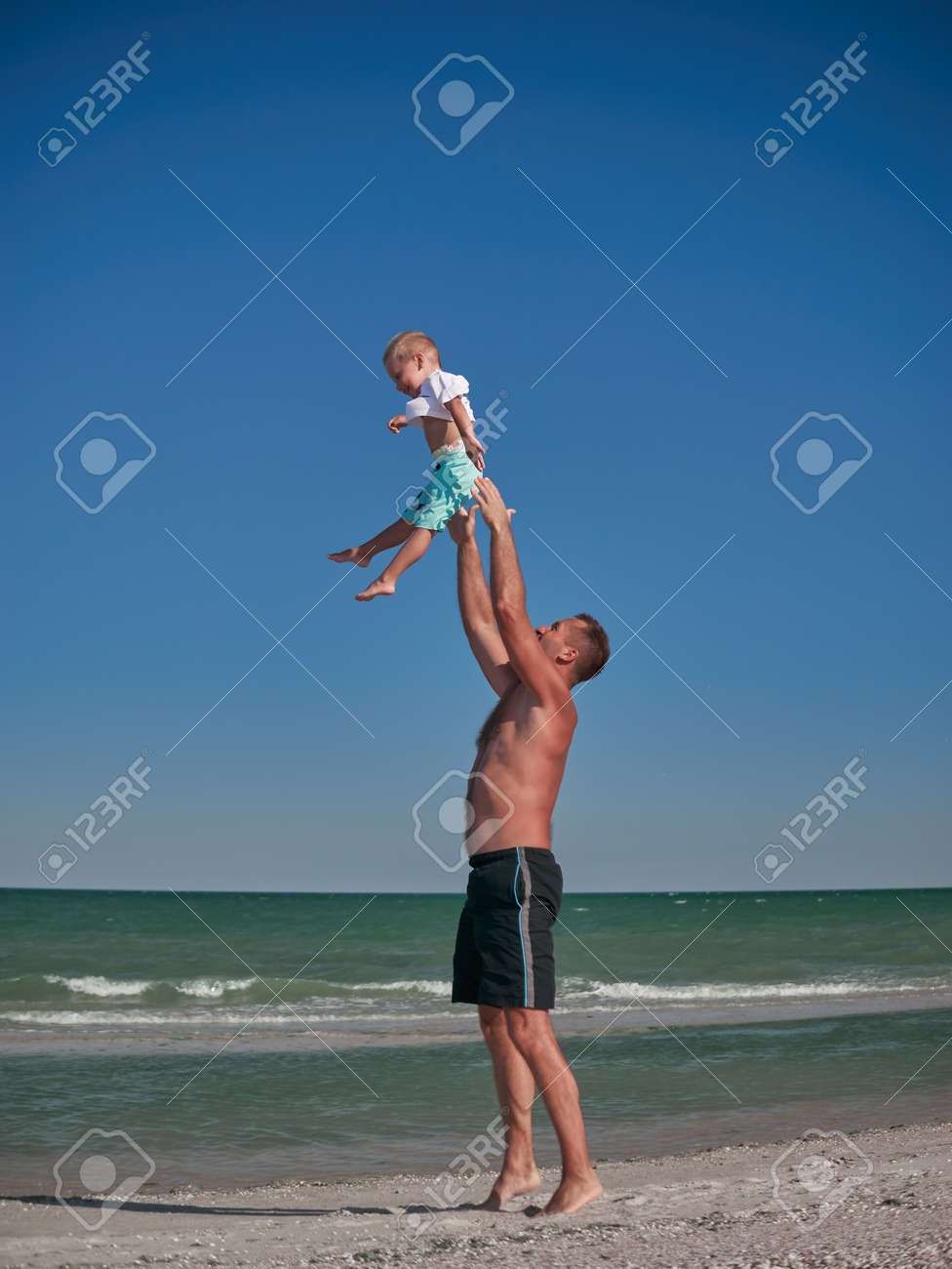 Dad And Baby Playing On Seaside In Summertime. Happy Family And ...