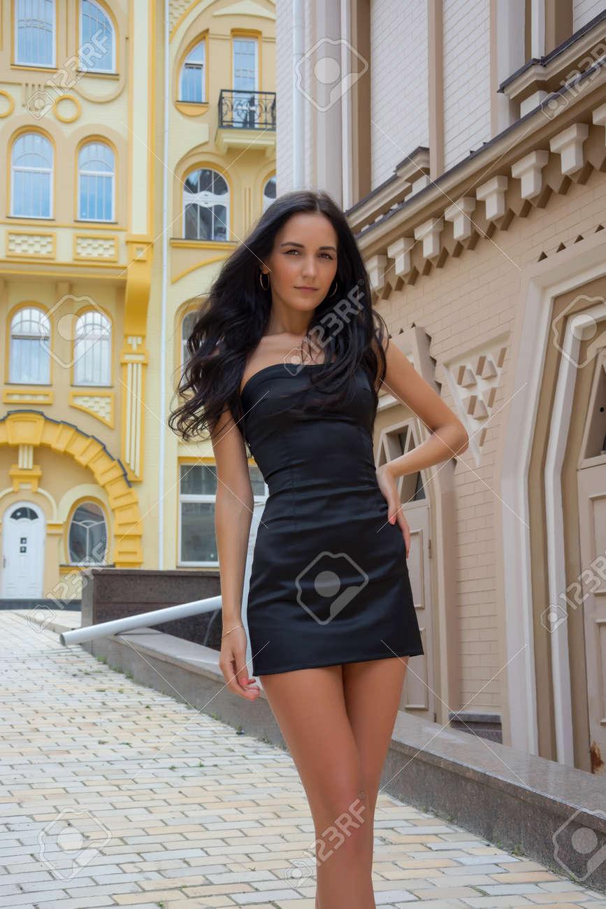 80eff76fac9 Banque d images - Modèle en petite robe noire en face de bâtiments colorés  dans une ville européenne Une jeune fille en face de foyers urbains