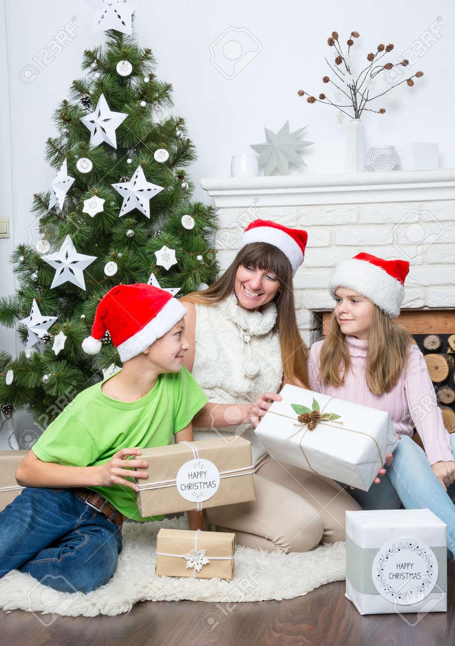 Regali Di Natale Alla Mamma.La Mamma Da I Regali Per Bambini Vicino A Un Albero Di Natale Famiglia Celebrare Il Natale