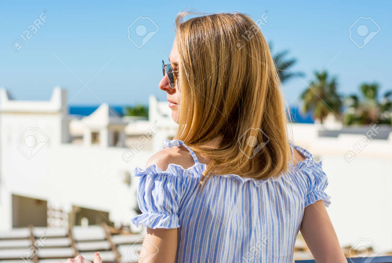 Young girl in sunglasses stands a back on the balcony and looks at the sea and palm trees. - 143071621