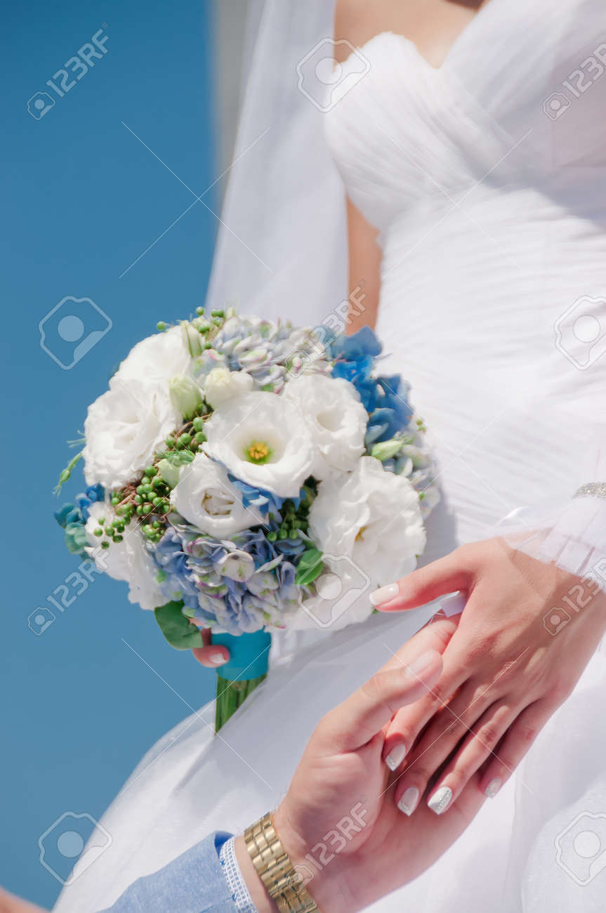 Hands With Wedding Rings And Beautiful Blue And White Fresh Flowers