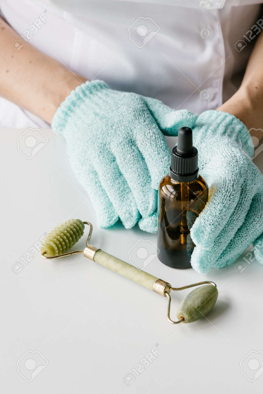Brown plastic bottle for liquid cosmetics in womans hands in green gloves, green jade massage roller on white table. Cosmetologist holding spin care products. - 152134220