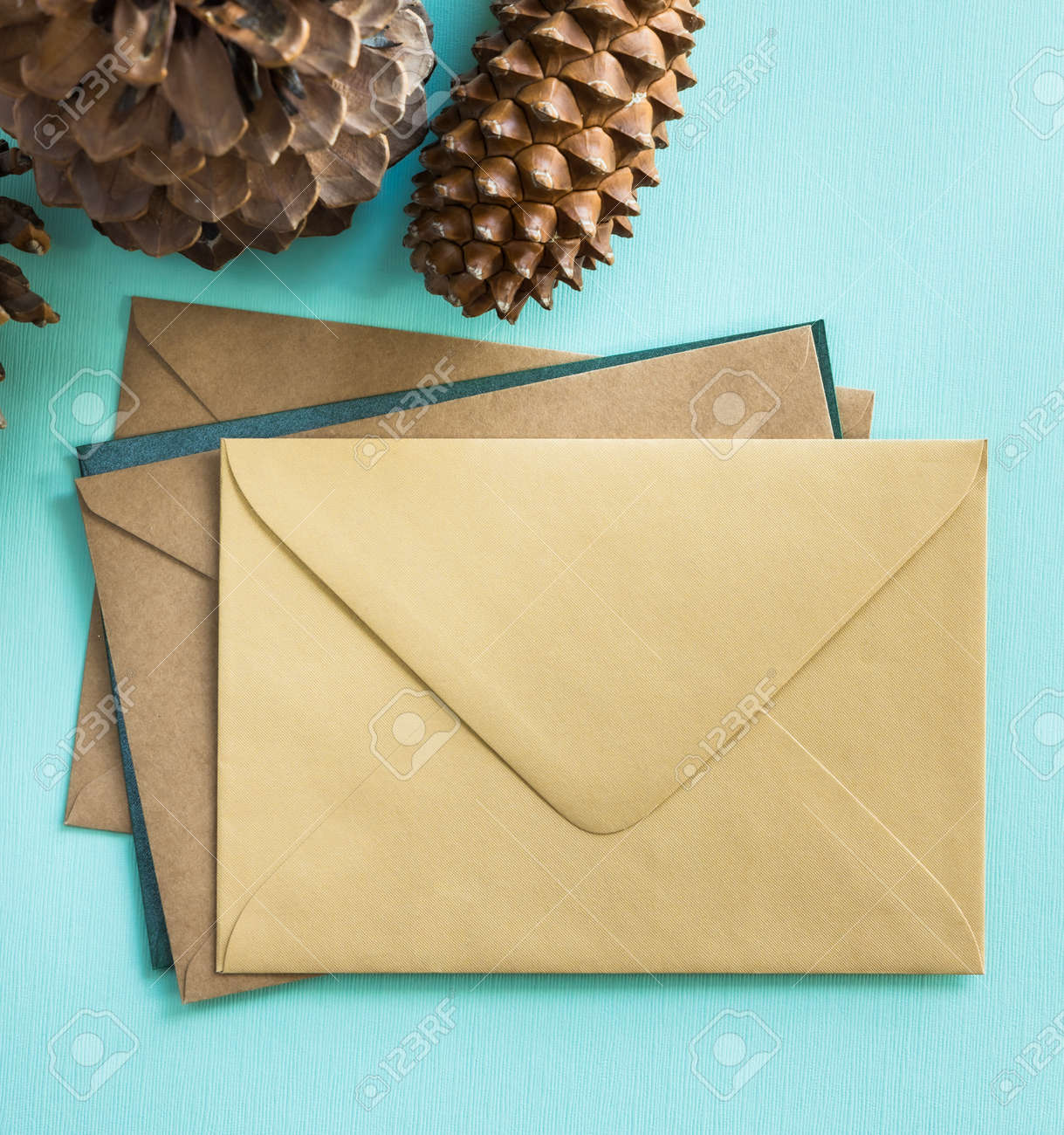 Many envelopes and pine cones on turquoise background. Winter holidays concept. - 156003956