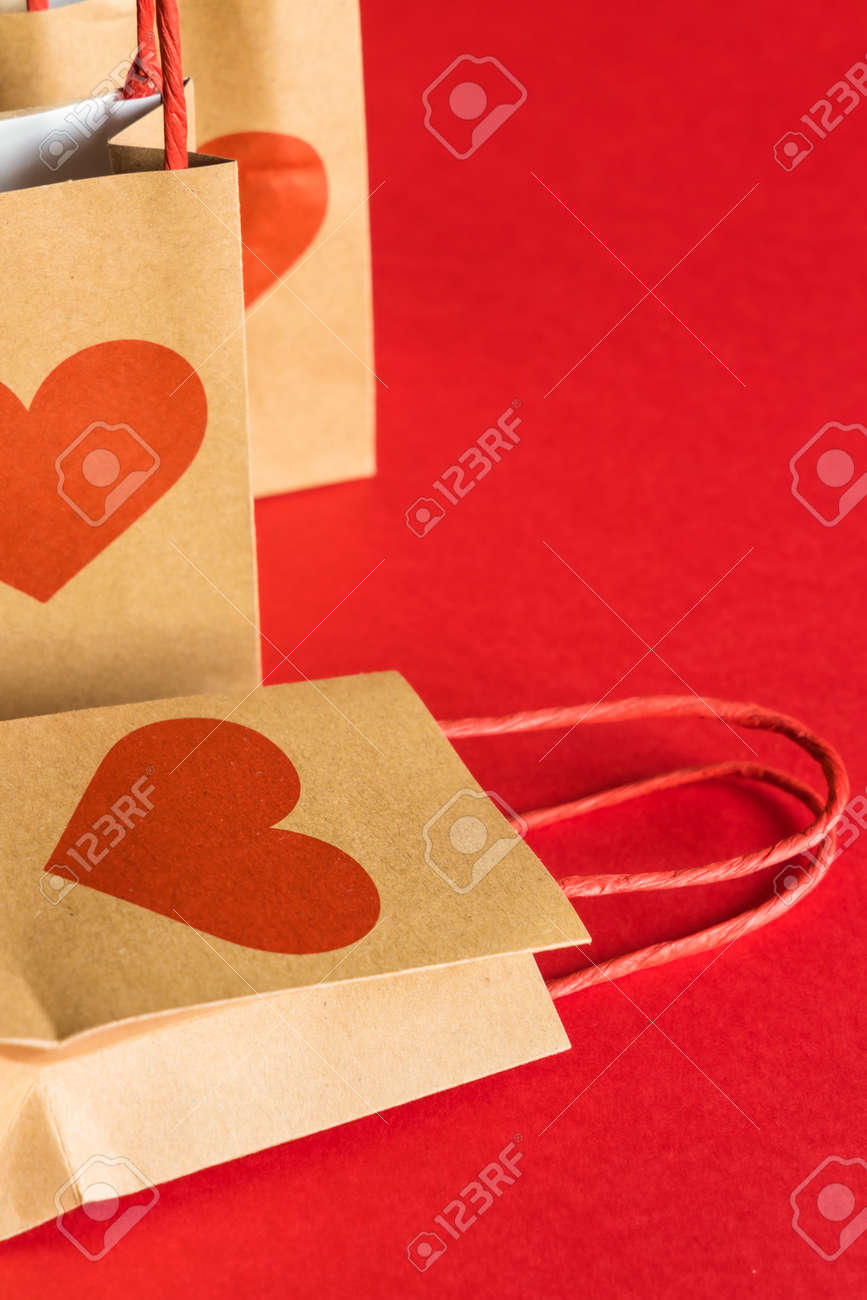 Valentines Day concept. Shopping paper bags with hearts print on red background. - 158366398