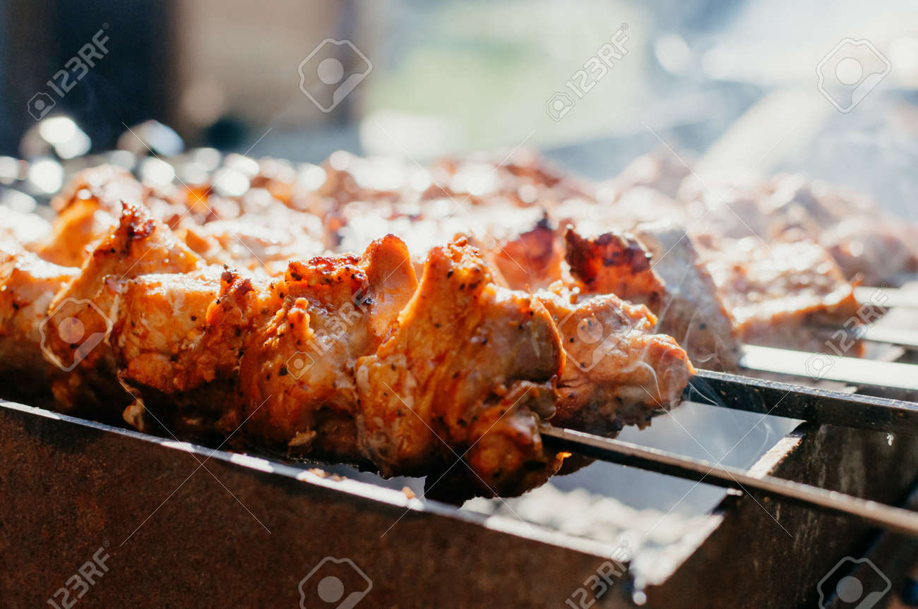 Cooking marinated pork kebabs on the grill. Fried pork kebabs on an open fire. Grill cooking season. - 169524230