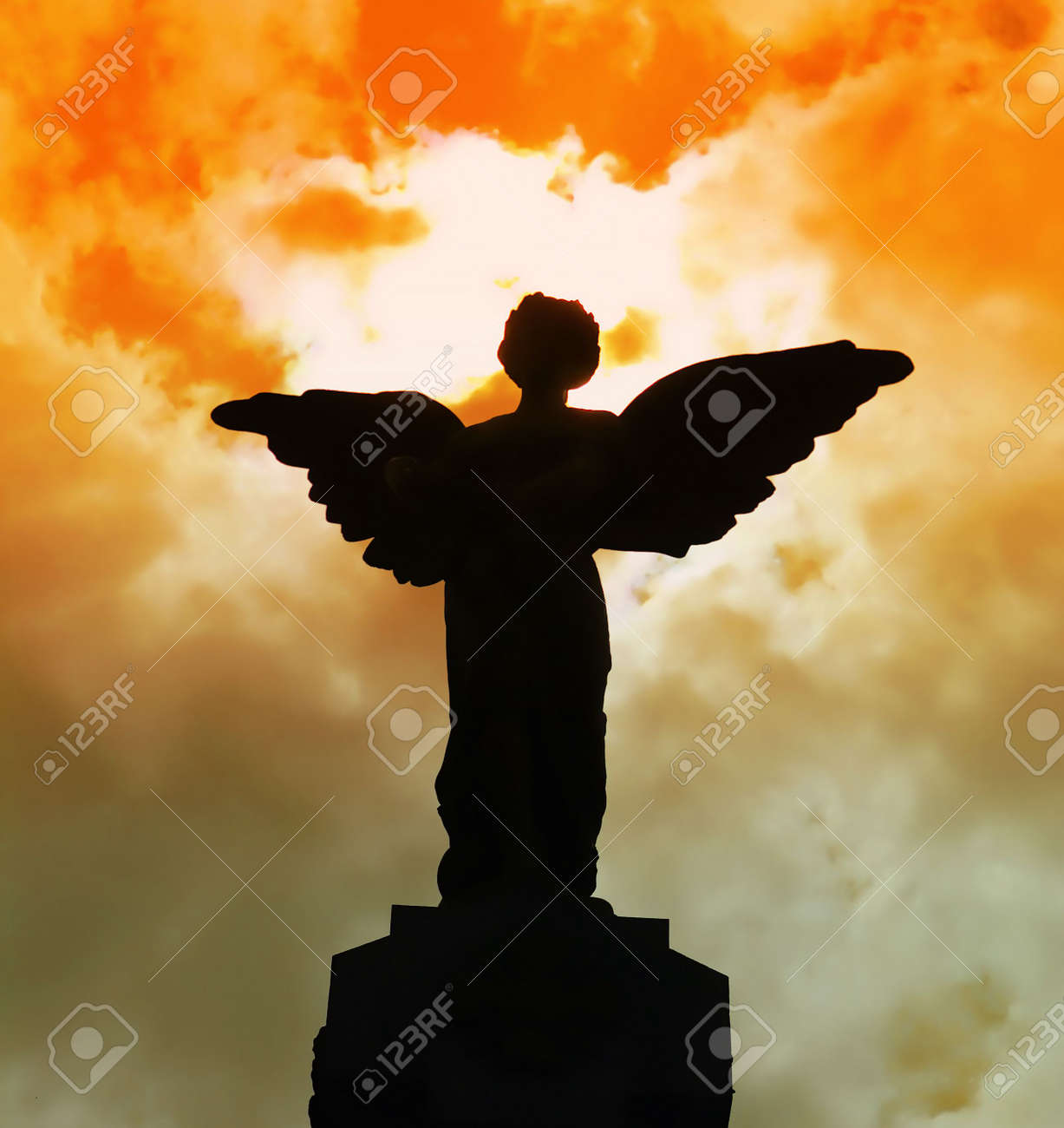 statue of an angel silhouetted against red clouds stock photo