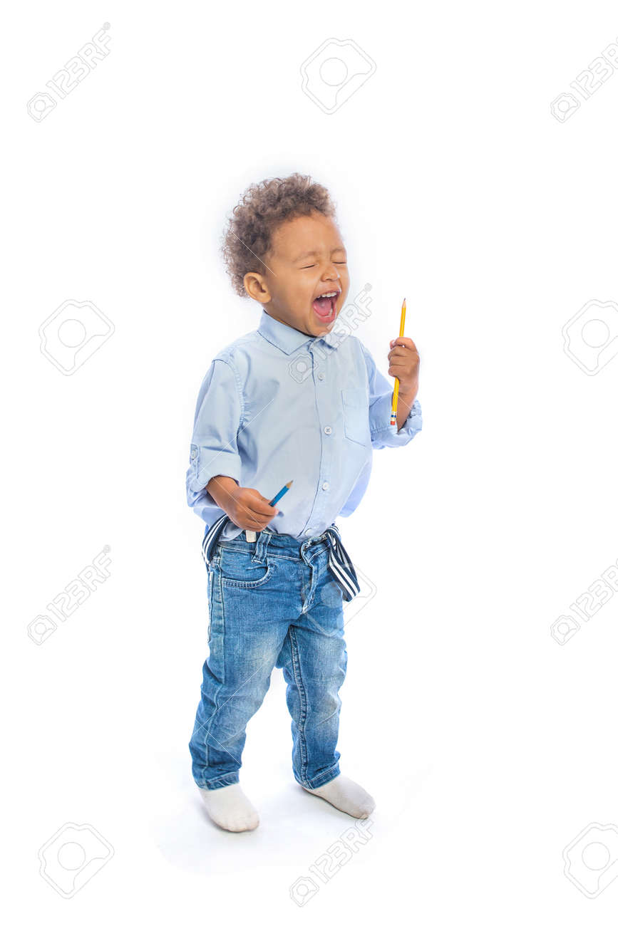 A Small Dark Skinned Boy With Curly Hair In Jeans And A Light Colored