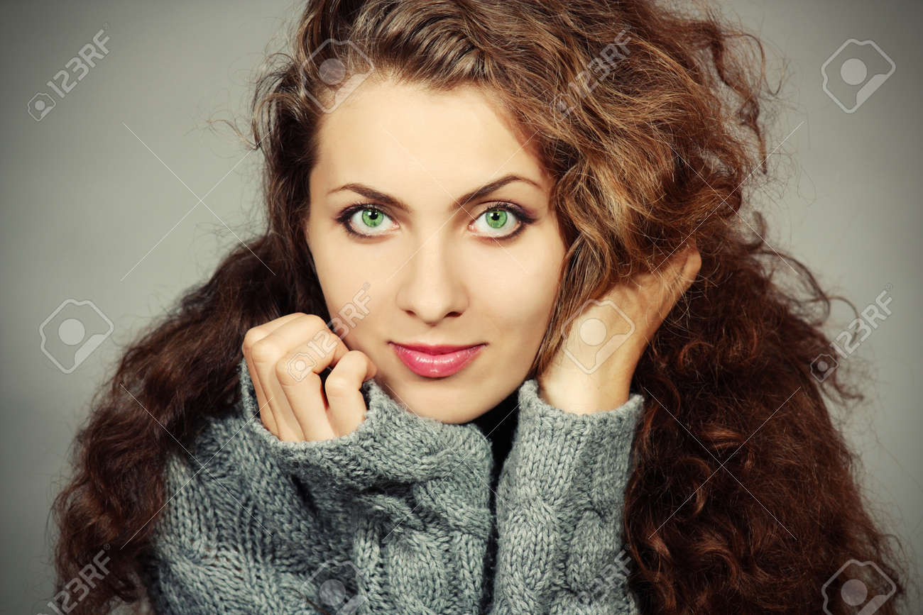 Beautiful young woman in a gray sweater with a gray background Stock Photo - 11746885