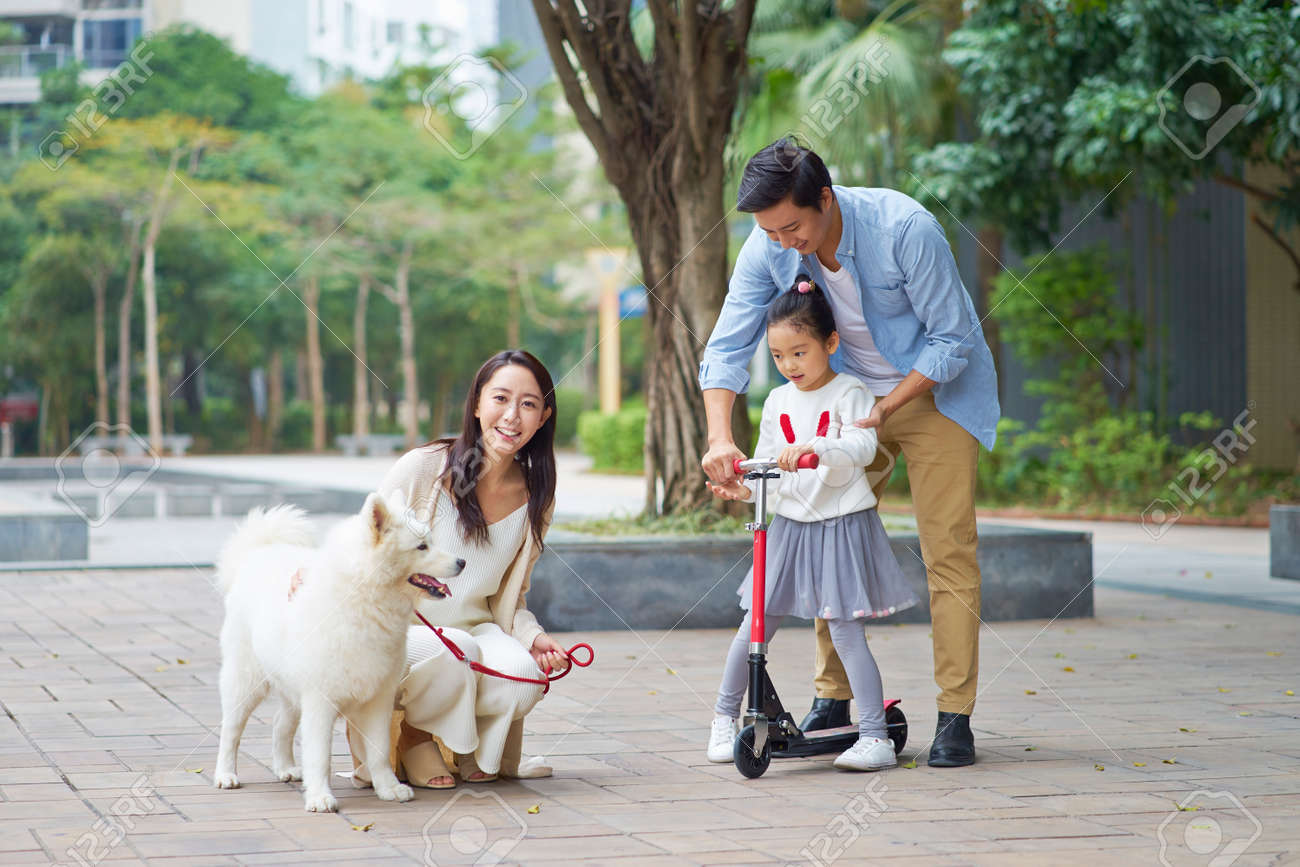Asian parents & daughter playing scooter while walking dog in