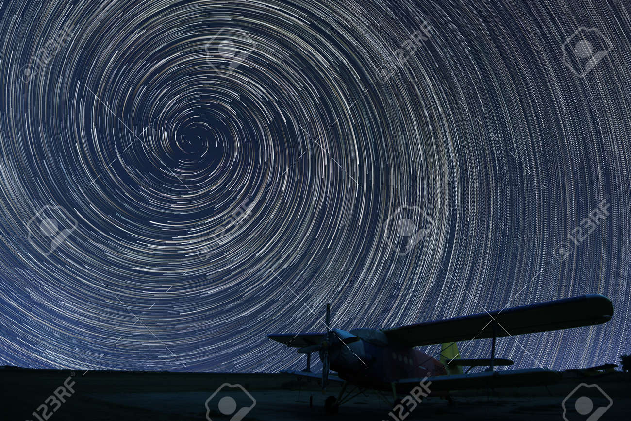 Beautiful night sky, Spiral Star trails over small airport lonely airplane. Vortex Star trails. - 44222274