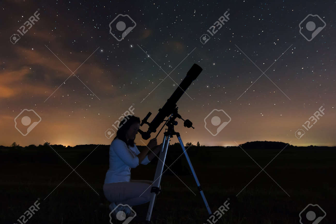 Woman looking through a telescope watching the stars. Woman under Night sky, constellations, Draco, Ursa Major, Big Dipper, Botes - 47066493