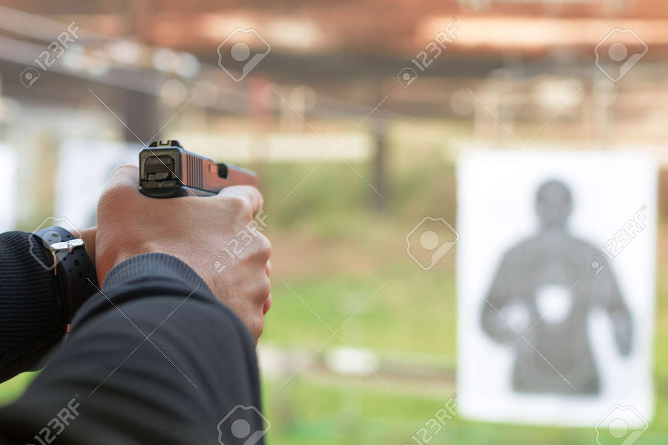 Shooting with a pistol. Man aiming pistol in shooting range. - 64481208