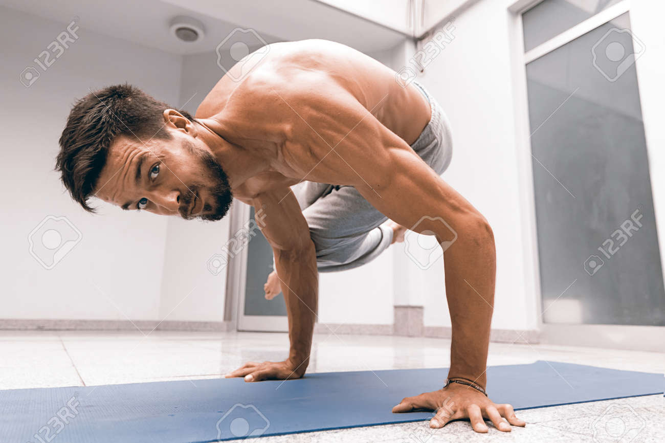 Athletic Strong Man Practicing Difficult Yoga Pose Stock Photo