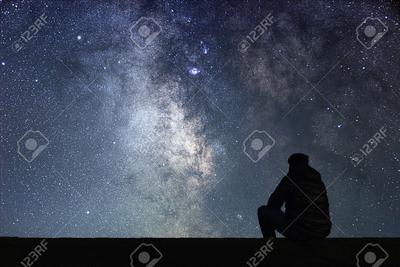 Man looking at the stars. Alone man looking at starry sky. Night sky. - 72100796