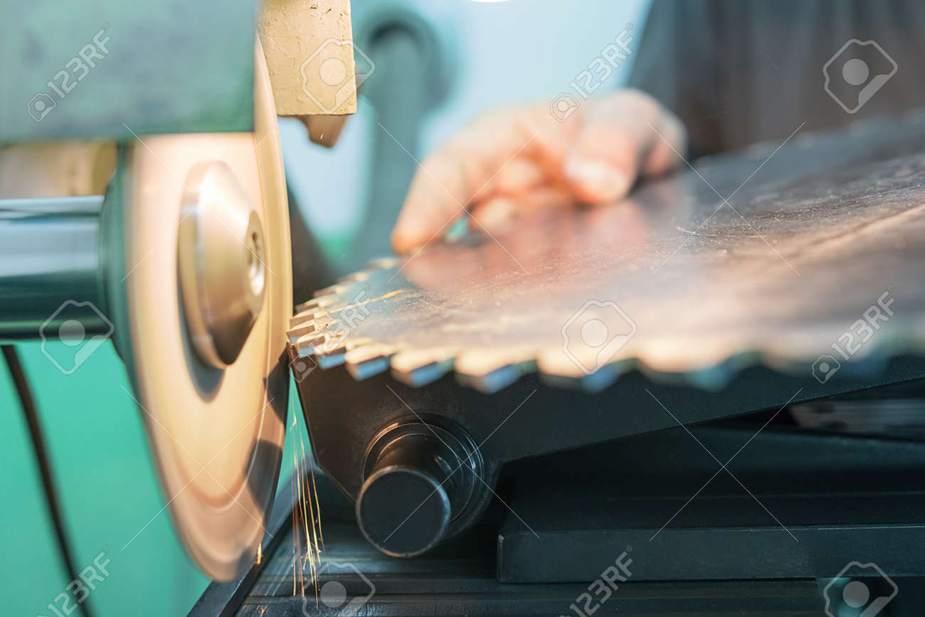 Sharpening Circular Saw, worker sharpens a circular saw blade