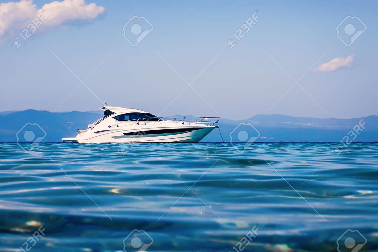 Motor boat floating on clear turquoise water - 118087450