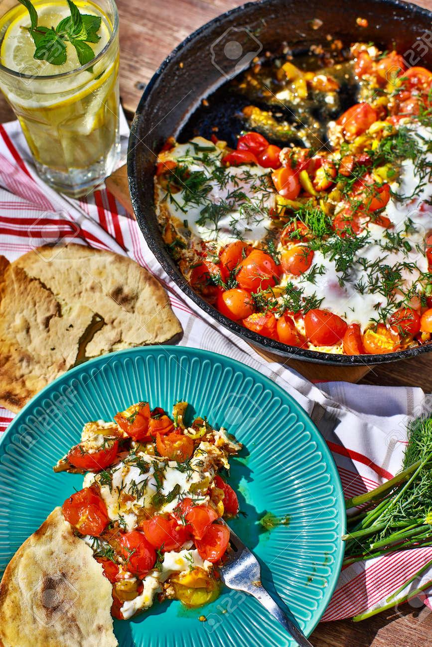 fried eggs with vegetables in a pan, vegetarian breakfast - 131069337