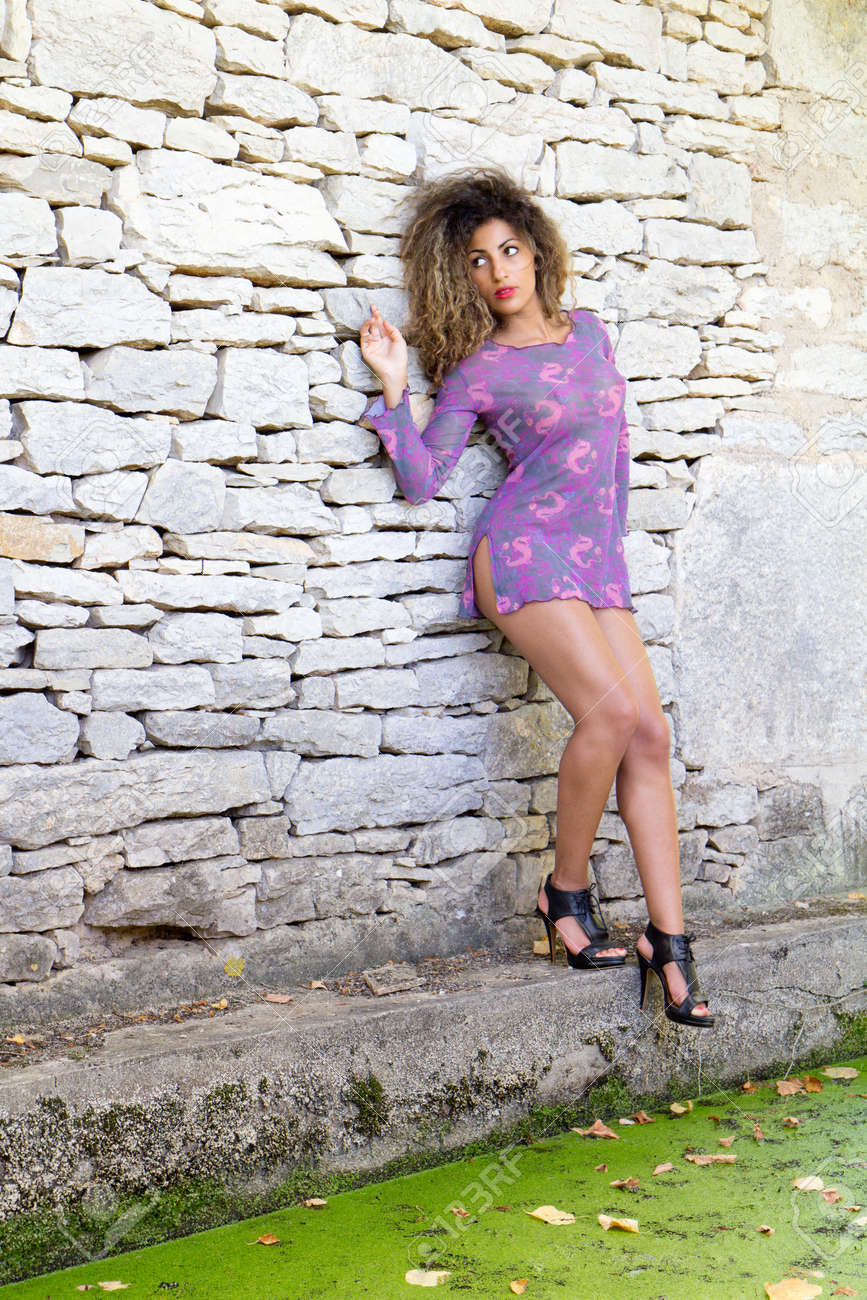 Sexy young woman in front of a wall and near a pond . She is wearing a short mauve dress and stilettos. Stock Photo - 10797194