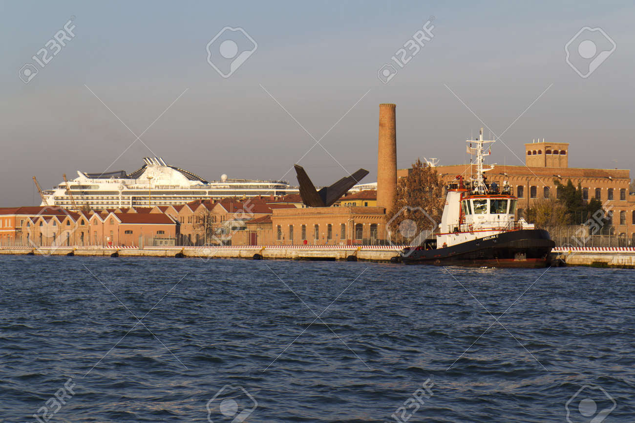 Venice, Italy - November 26, 2011: a tugboat is moored  in the port. Behind , we can see a factory and a liner.  Stock Photo - 11652066