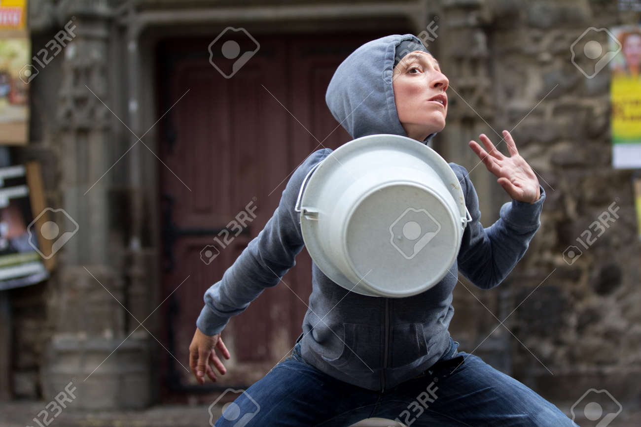 AURILLAC, FRANCE - AUGUST 23: a dancer puts a bucket around her neck as part of the Aurillac International Street Theater Festival, show named Vachement, on august 23, 2012, in Aurillac,France. Stock Photo - 15131896