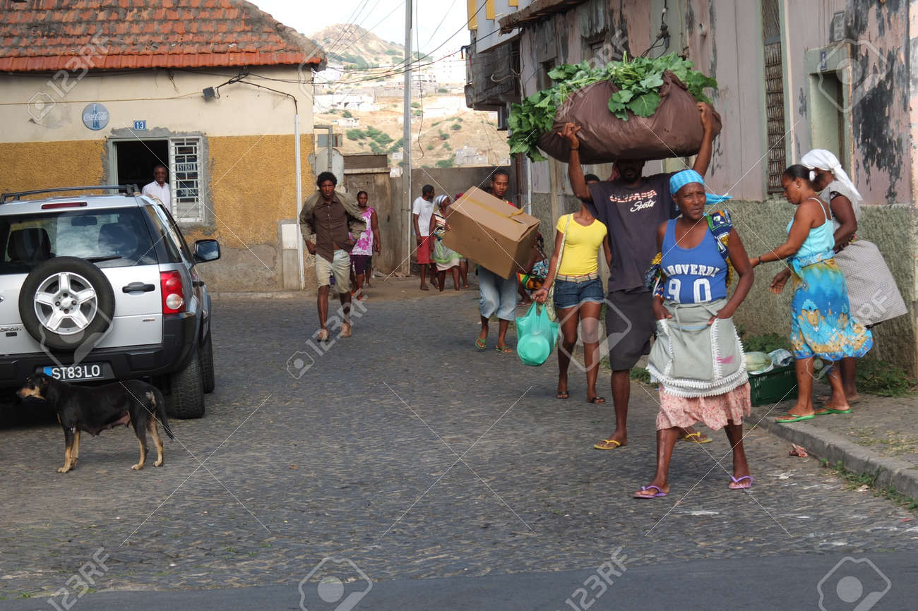 Praia, Cape Verde - November 26: some African people is carrying goods to sell at the market.Everyone is coming on foot. Stock Photo - 16972861