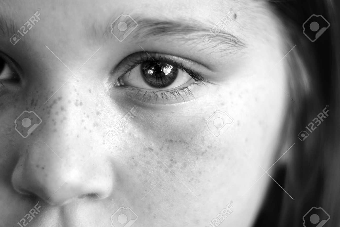 Black and white closeup of a girls face with expressive eyes reflections in eye