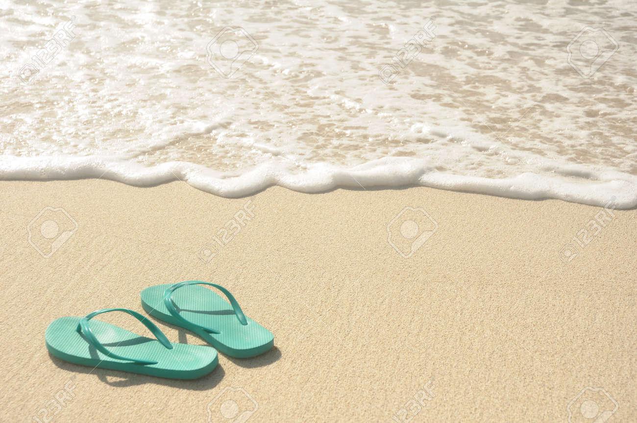 Green Flip Flops on a Sandy Beach Stock Photo - 13042235