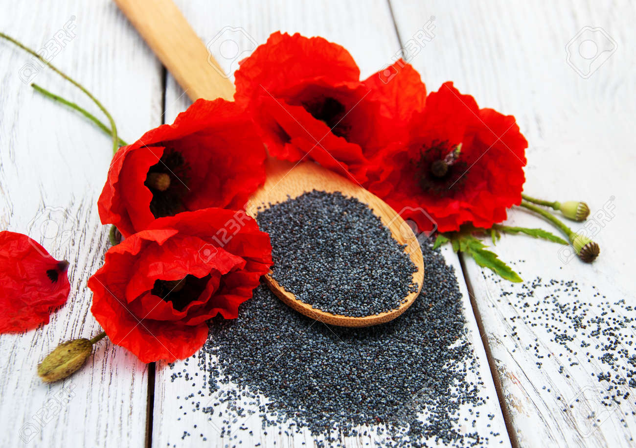 Poppy Seeds And Poppy Flowers On A Wooden Background Stock Photo