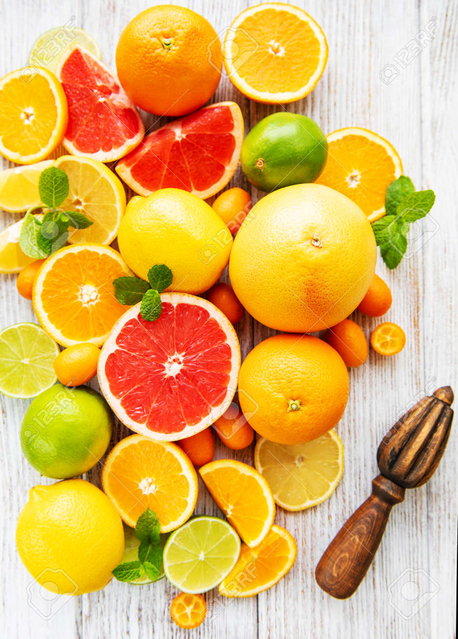 Fresh citrus fruits on a old wooden background - 121917485
