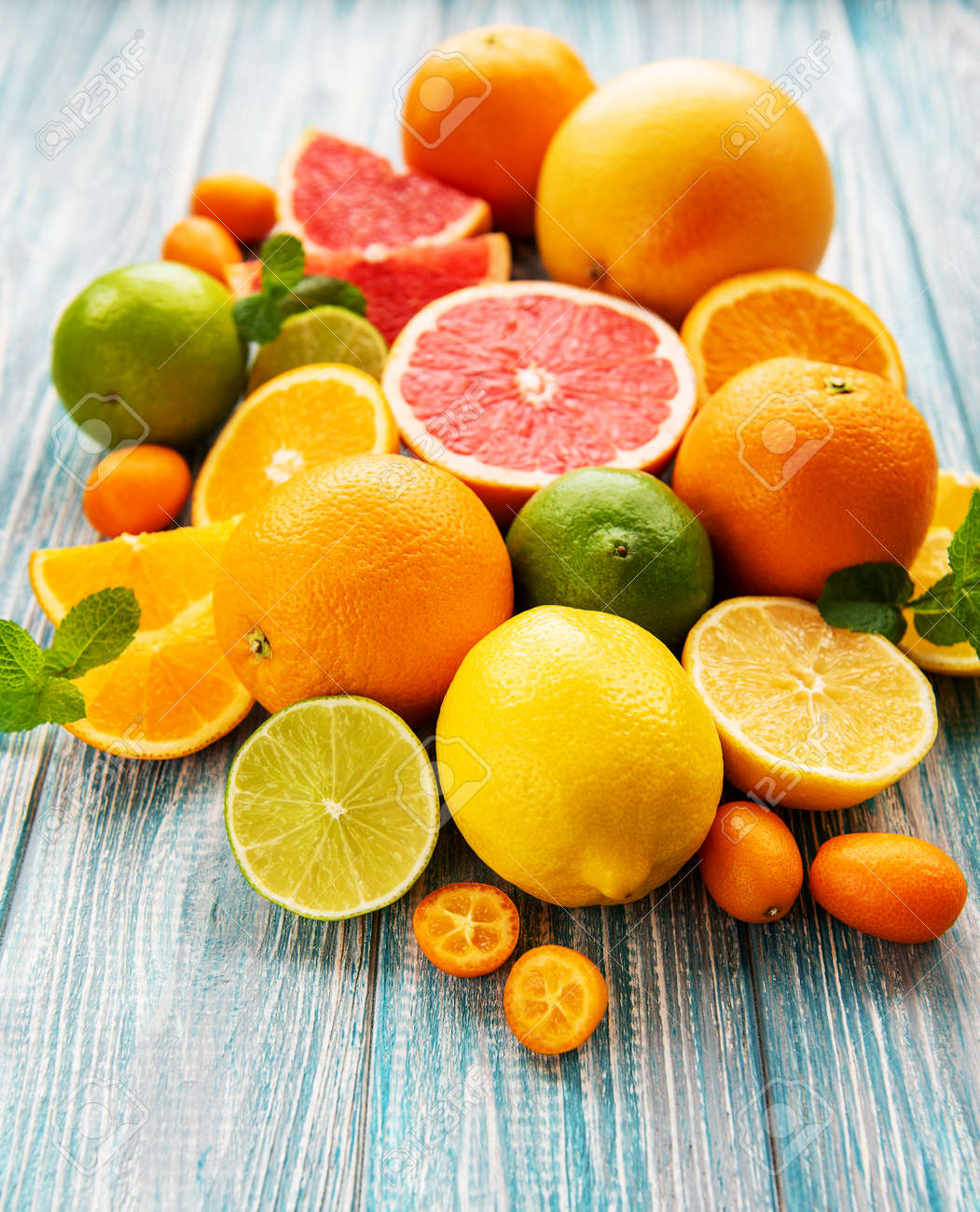 Fresh citrus fruits on a old wooden background - 123625226