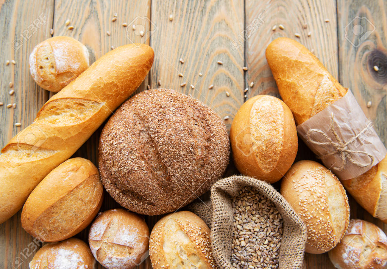 Assortment of baked bread on white wooden background - 130595230