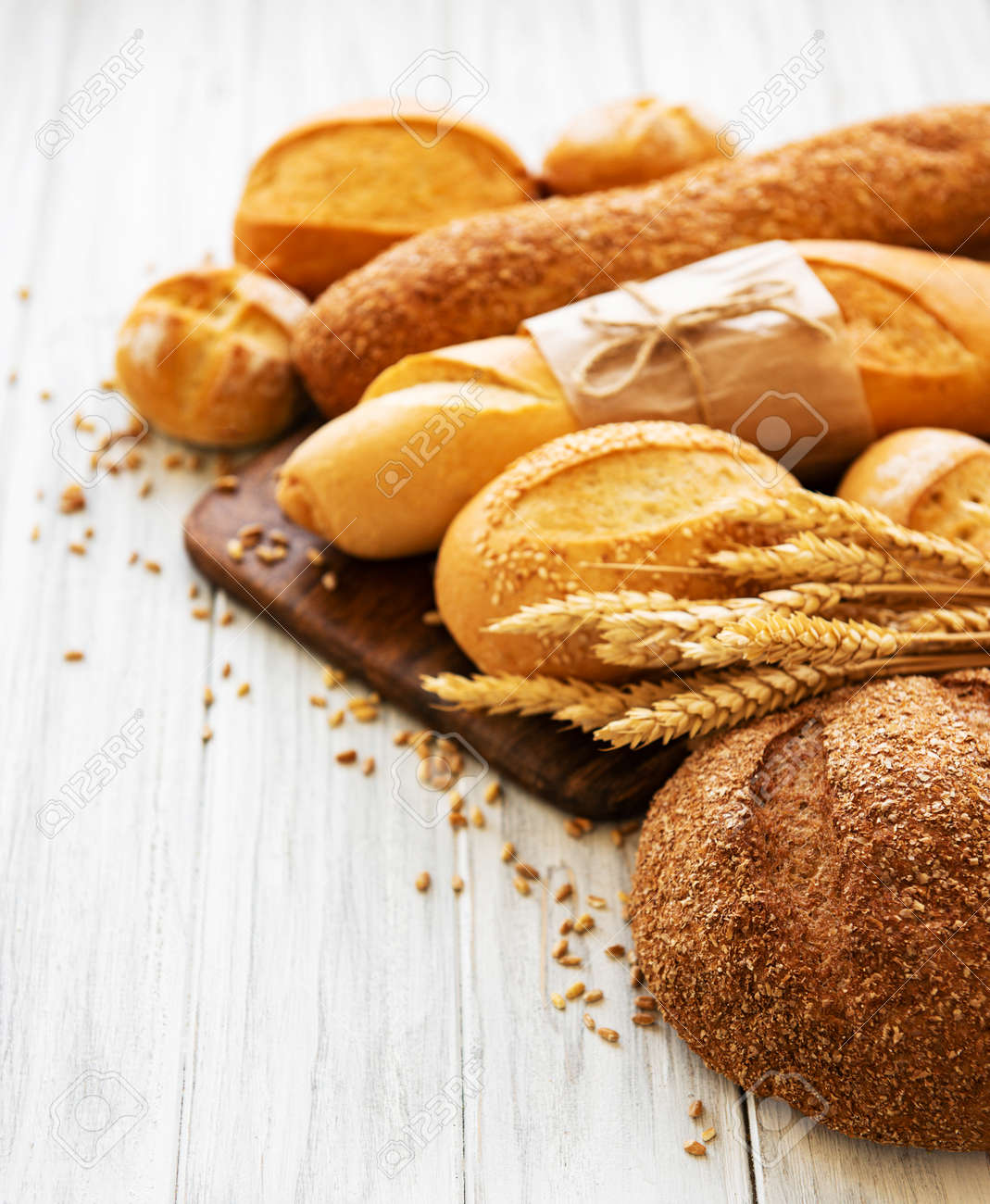 assortment of baked bread on white wooden background - 134599635