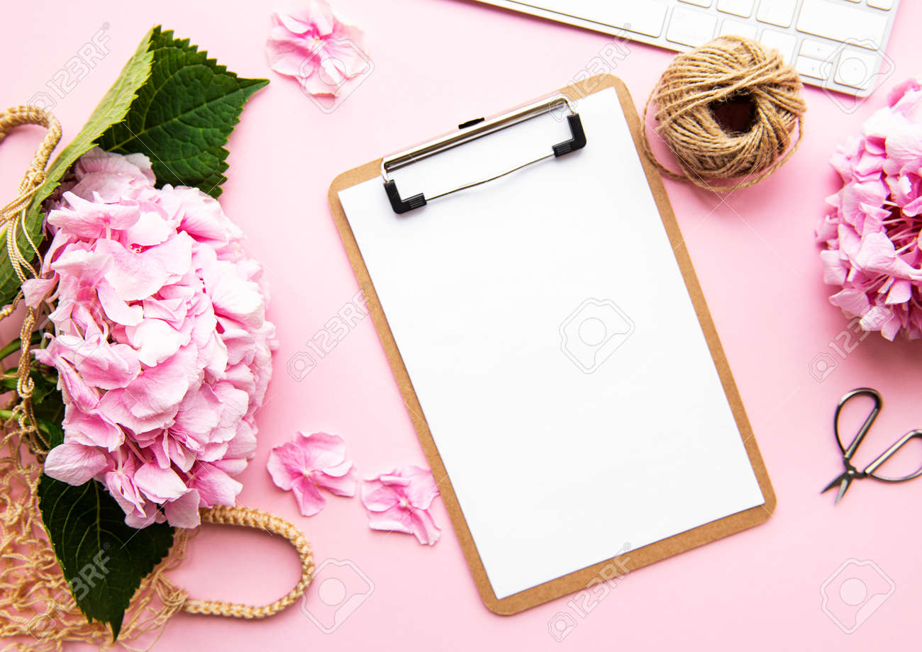 Beauty composition with clipboard, hydrangea and accessory on pink background. Top view. Flat lay. Home feminine desk. - 138827078
