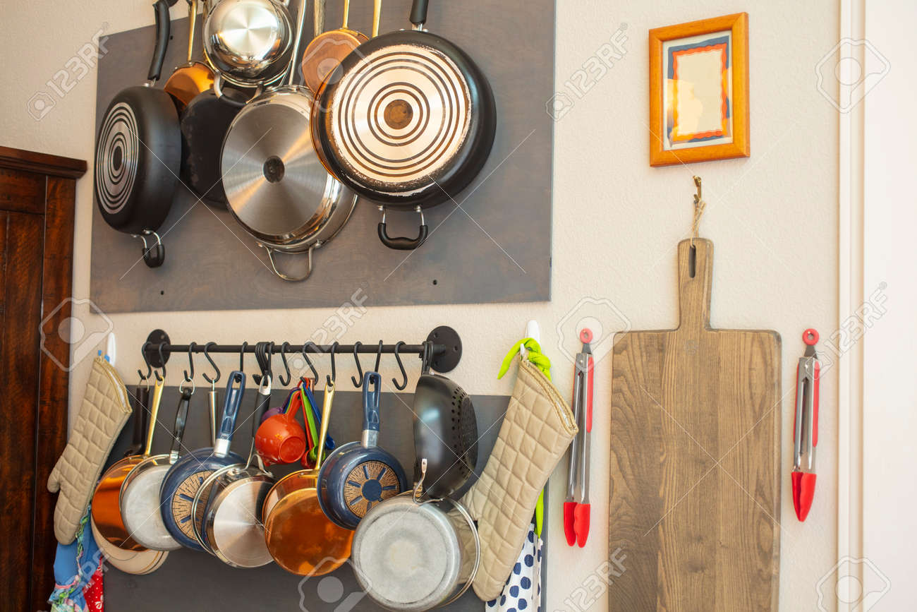 Kitchen wall rack for hanging pots, pans, aprons, and other utensils..
