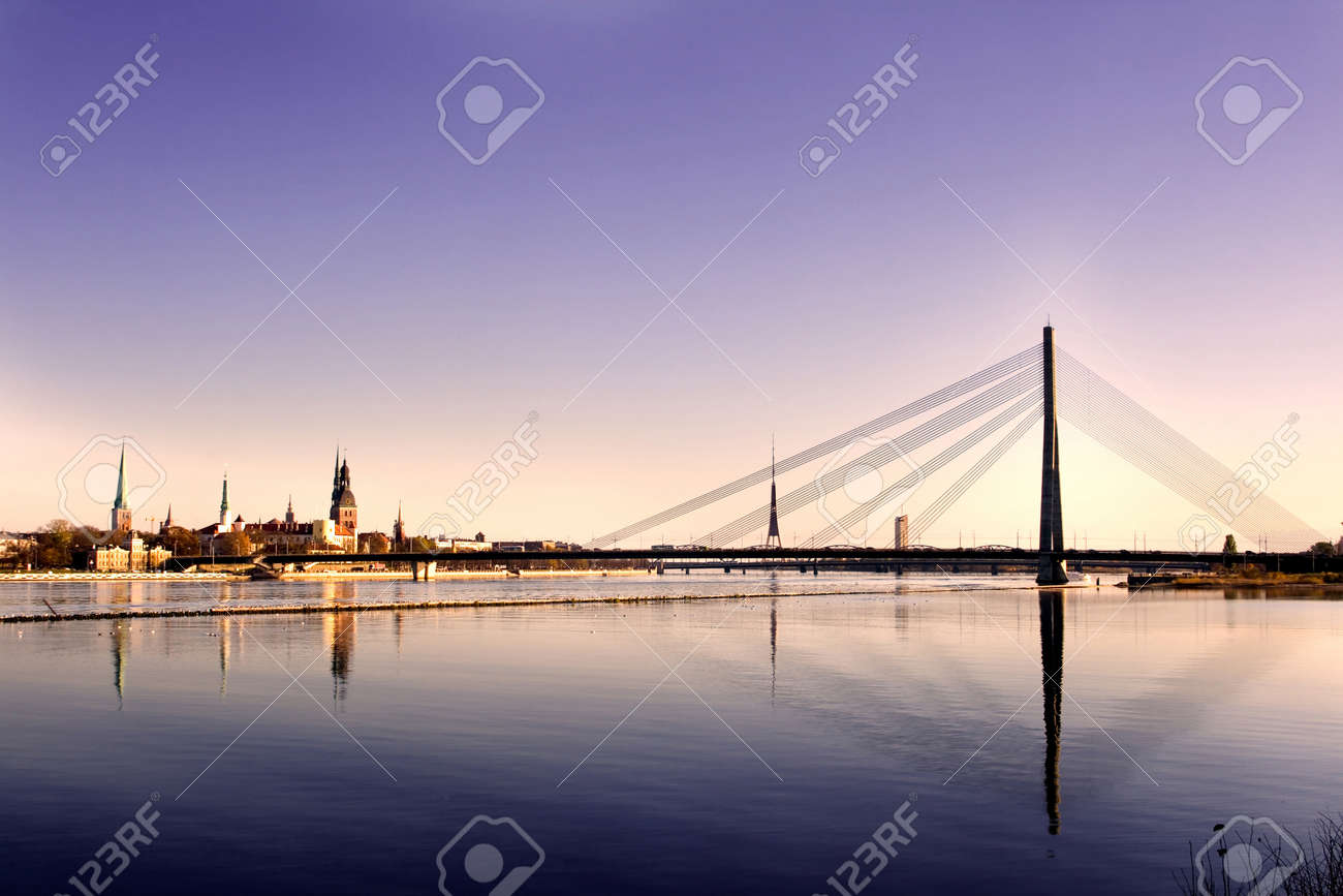 Classic view of Old Riga in Latvia. Cable-stayed bridge over the river of Daugava and Riga castle with Riga Cathedral in a front. TV tower, railway bridge and Saint Peter's church in a background. - 9413573