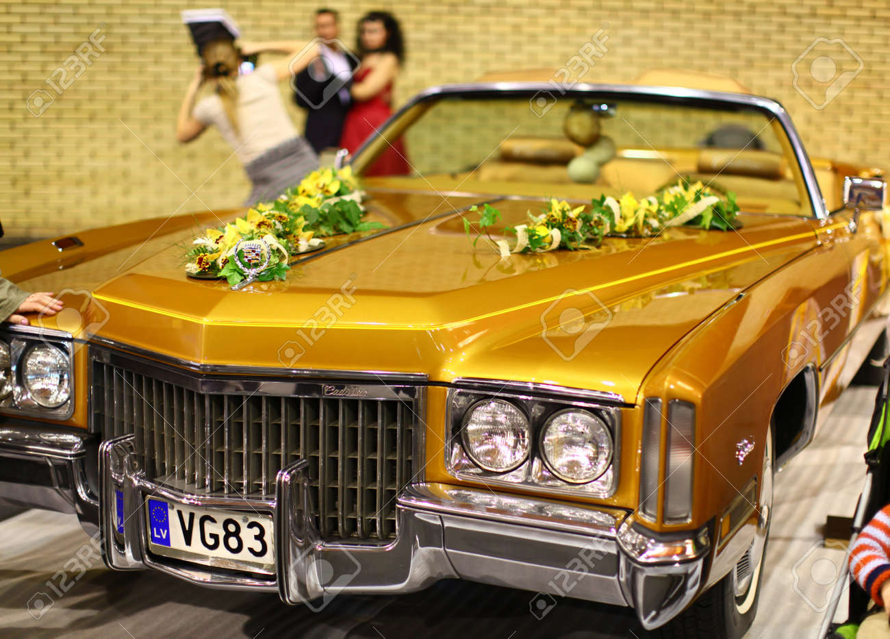 RIGA - APRIL 10: Model showcases of extravagant brides on the catwalk during Fiesta Expo 2011. Beautiful old Cadillac in fashion show in hall of Kipsala - April 10, 2011 in Riga, Latvia. Stock Photo - 9434055