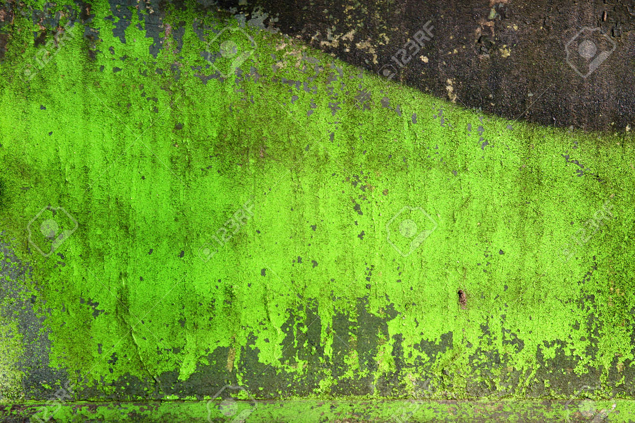 Grunge background / texture on a cracked green stone wall with splashes of paint. - 9485259