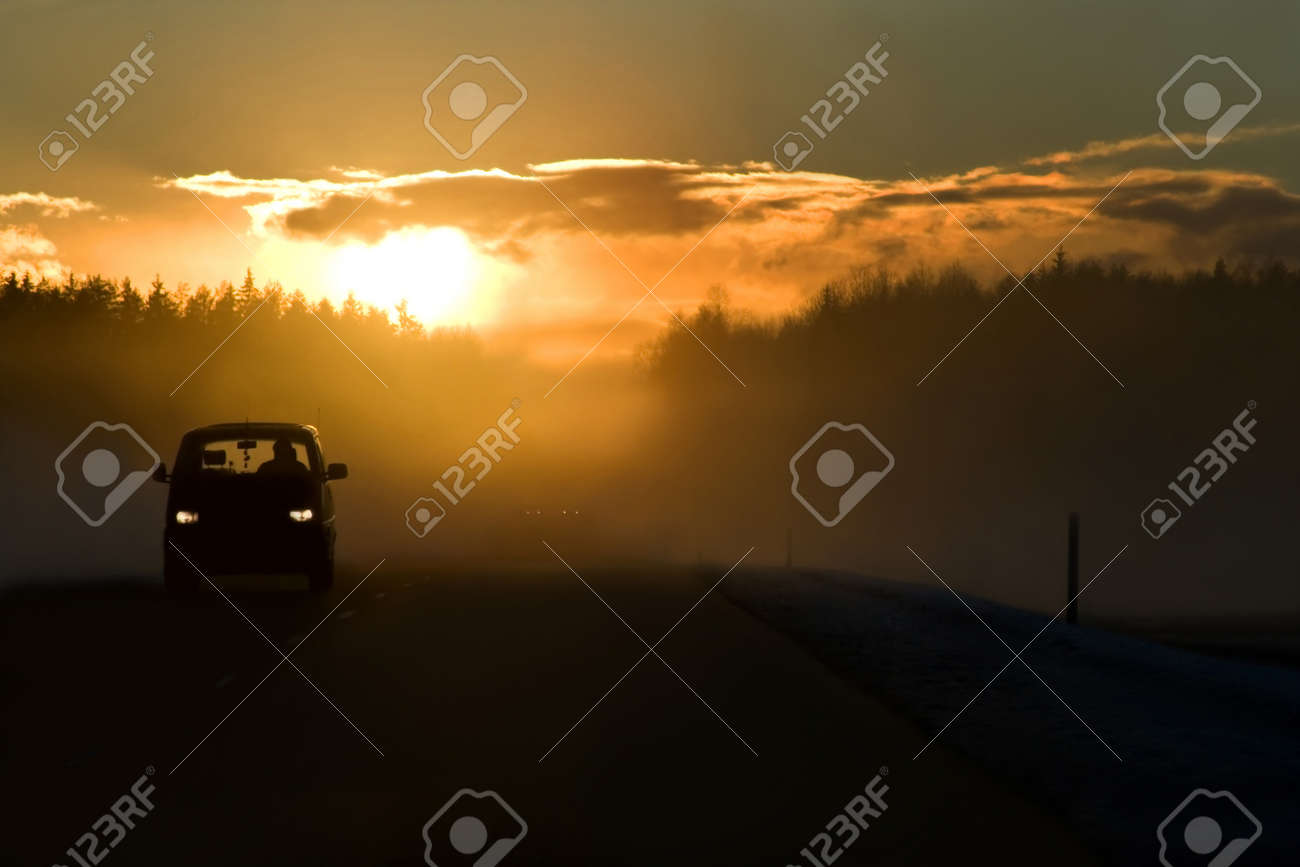 Fog on the road at the start of winter. Bright sun in clouds, minivan on the left side of road and dangerous overtaking in the background. This is E22/A10 winter road Riga - Ventspils. - 9828429