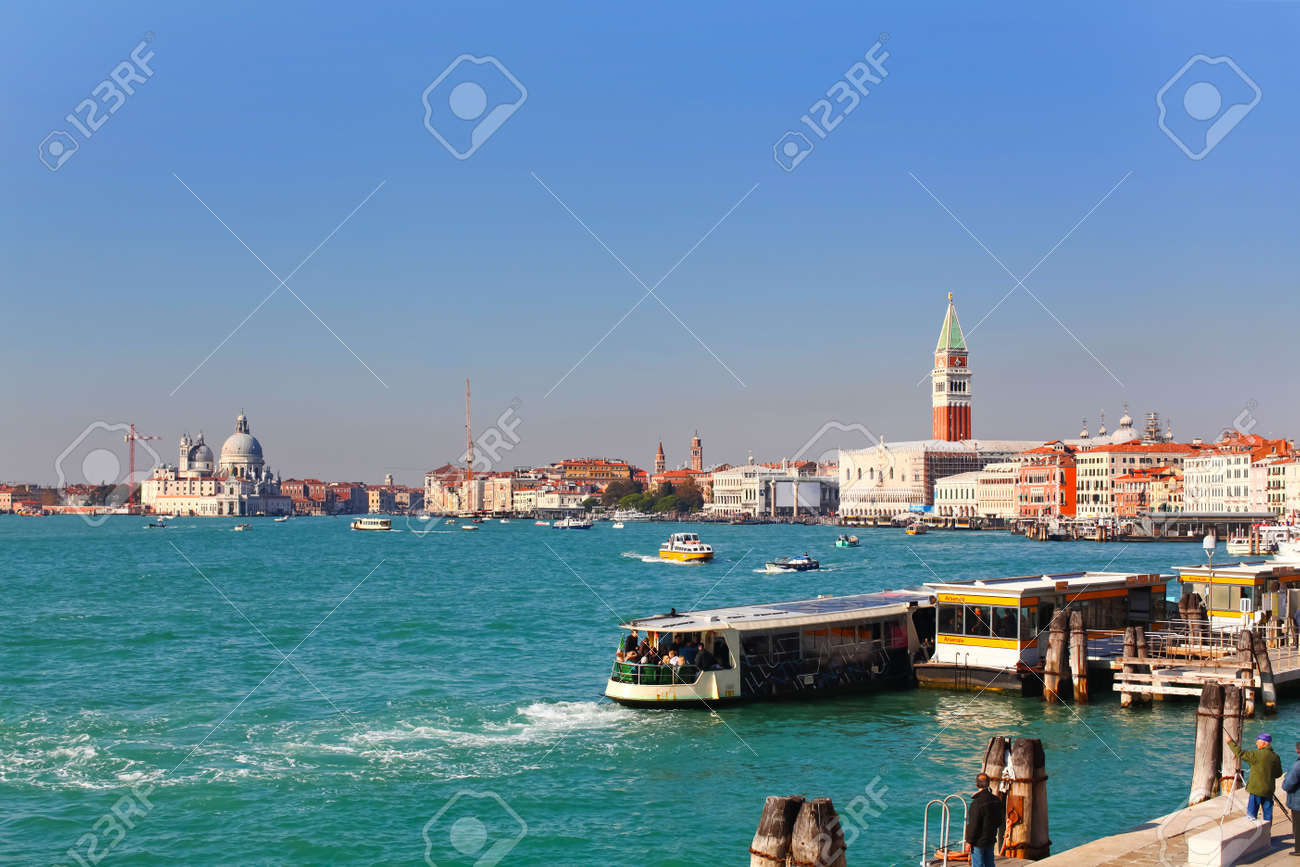 City life on famous Grand Canal in Venice, Italy  Vaporetto station is in front  Basilica di Santa Maria della Salute to the left and Campanile San Marco to the right  Stock Photo - 12734245