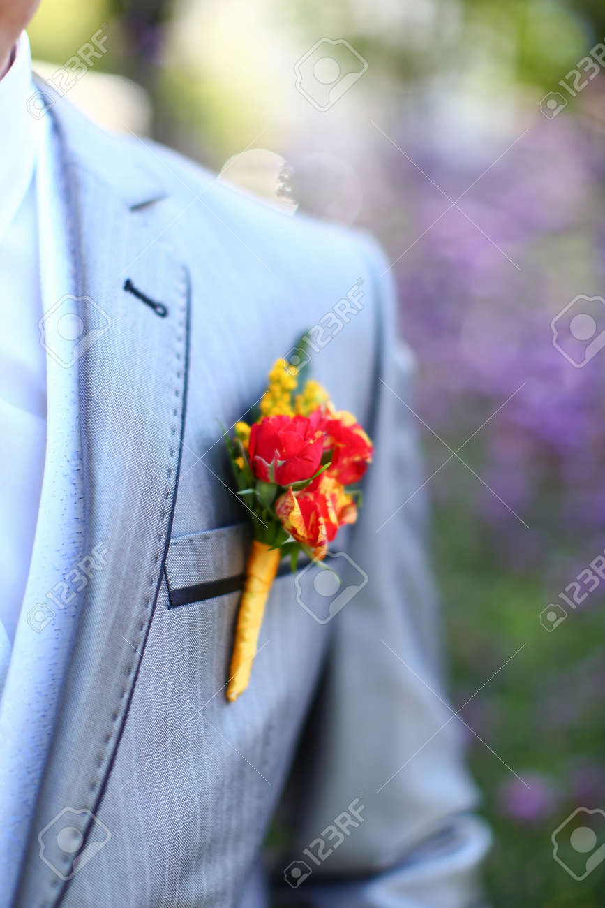 Wonderful wedding boutonniere on a costume of groom from beautiful colorful flowers. Nice bokeh in the background. - 12904775
