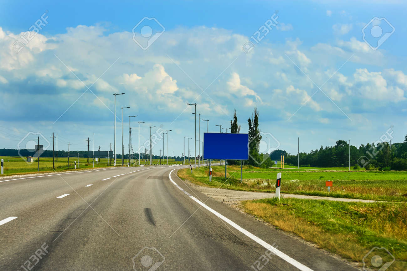 European route E67 it s part of Via Baltica road in countryside of Lithuania with beautiful clouds and fields - 19740674