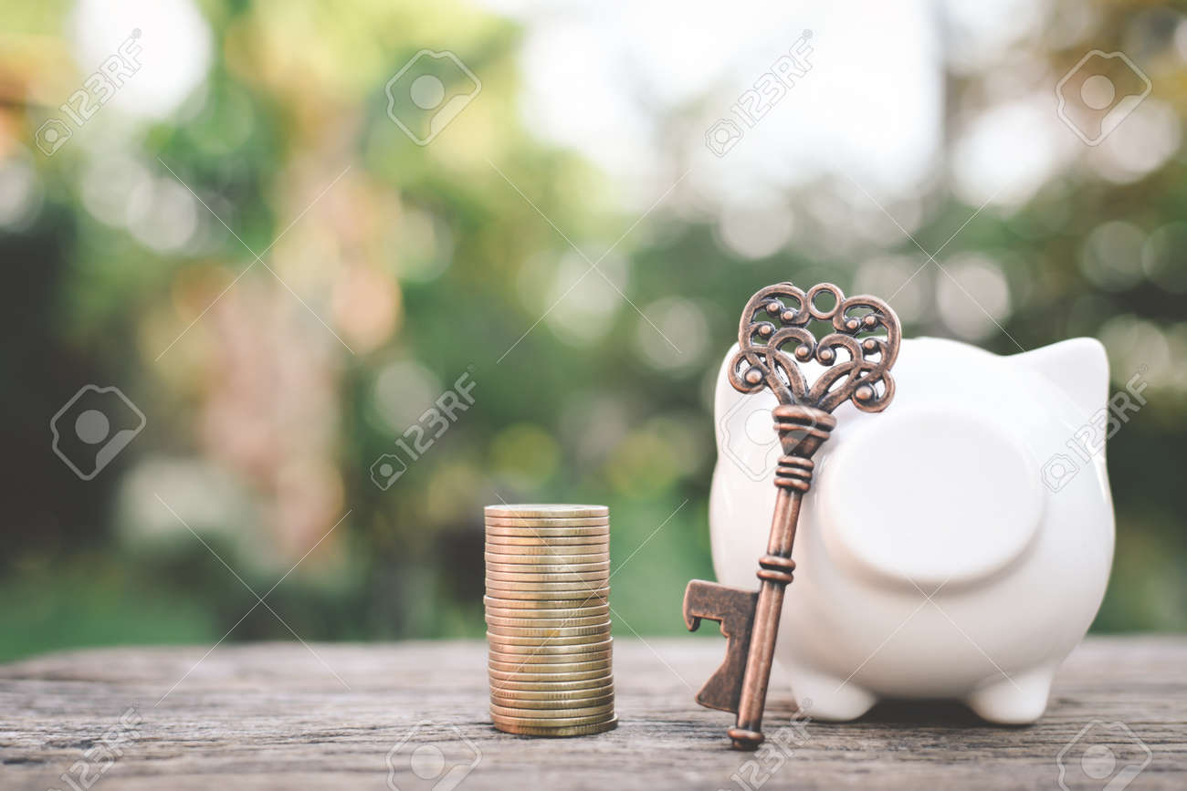 Old key coin piggy bank on wood a bokeh background with copy space a color of vintage tone selective and soft focus, concept save money Stock Photo - 73525771