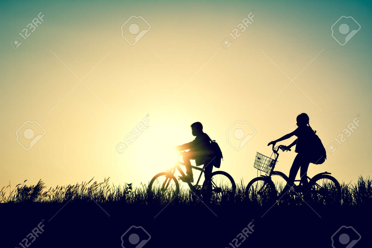 Silhouette of children with bicycle on grass field at the sky sunset, color of vintage tone and soft focus concept journey in holiday Stock Photo - 73525821