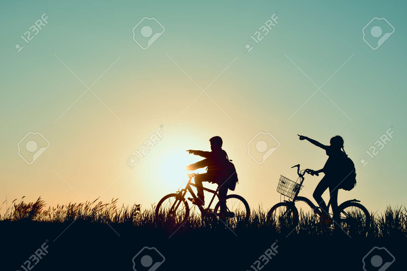Silhouette of children with bicycle on grass field at the sky sunset, color of vintage tone and soft focus concept journey in holiday Stock Photo - 73525822
