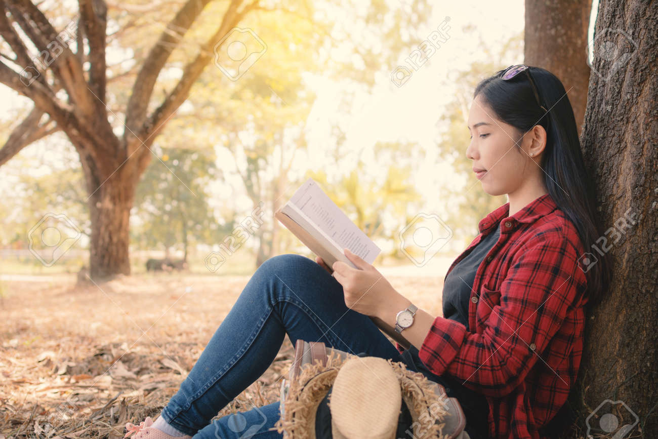 enjoying moment hipster woman reading a book and sitting under