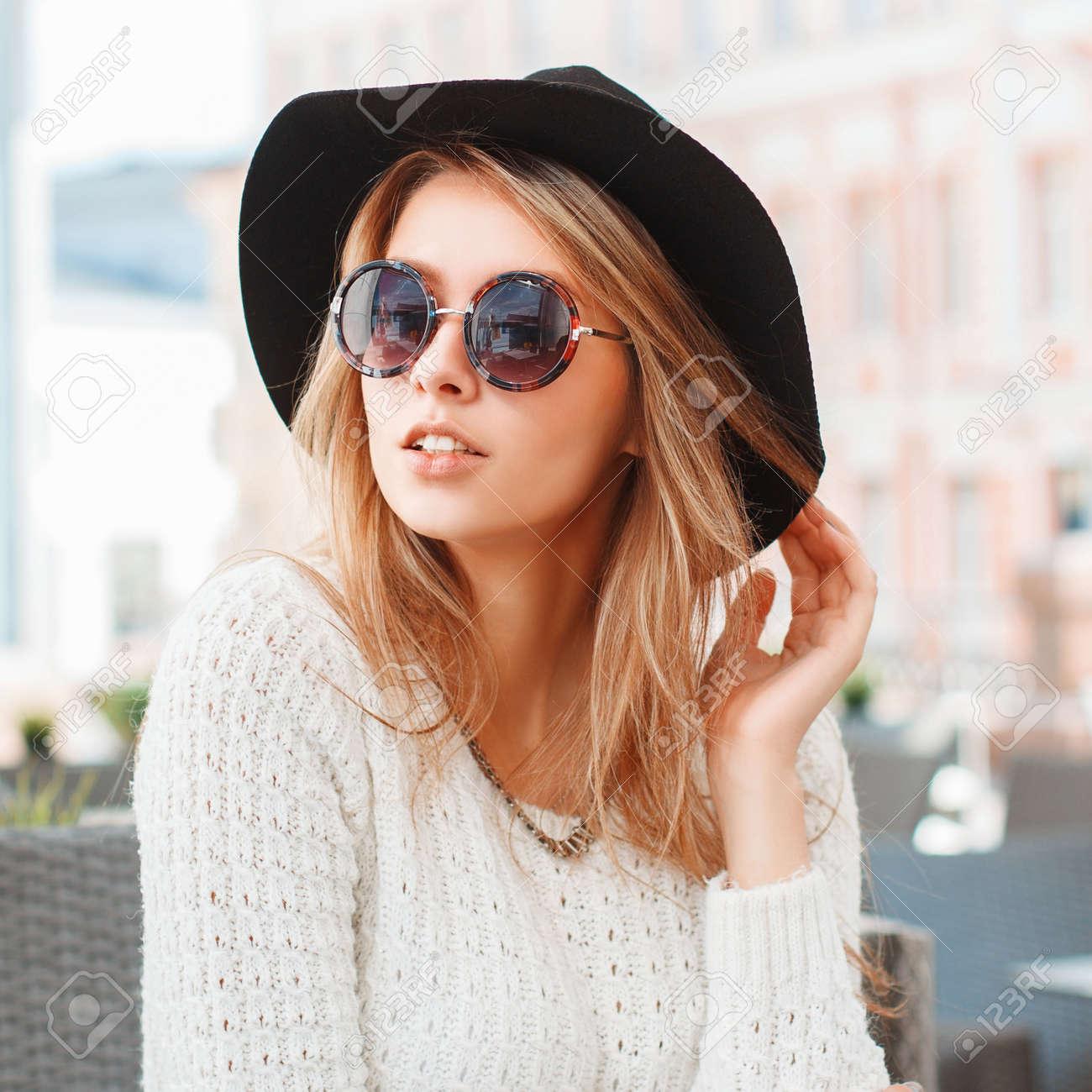 65560fd46b752 Banque d images - Femme à la mode avec chapeau noir et lunettes de soleil  rondes au café.