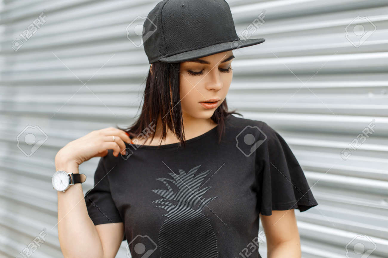 Beautiful cute girl in stylish black cap on a background of a metal wall  Stock Photo 163474e73a1